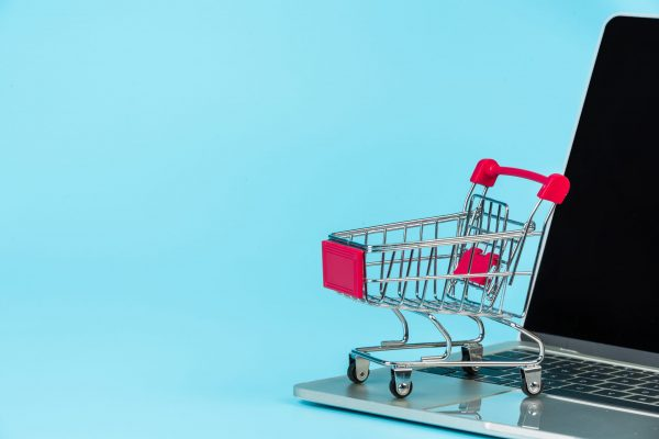 Online shopping concept, a shopping cart placed alongside a notebook on a blue background.